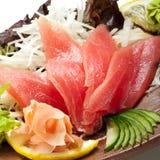 Tuna Sashimi. Maguro (fresh raw tuna) on Daikon (White Radish). Garnished with Ginger, Wasabi, Seaweed, Cucumber, Salad Leaf and Lemon royalty free stock photo