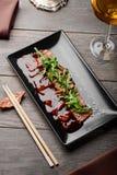 Tuna sashimi, chopsticks and wine. Tuna sashimi on black rectangular plate, chopsticks and glass of white wine on wooden table. Luxurious dinner in Asian royalty free stock image