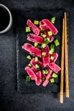 Tuna sashimi poke. With raw fresh fish, cucumber, black sesame seeds and soy sauce, black stone background copy space royalty free stock photos