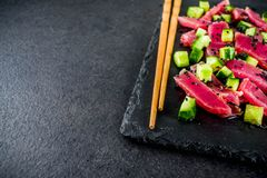 Tuna sashimi poke. With raw fresh fish, cucumber, black sesame seeds and soy sauce, black stone background copy space stock image