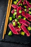 Tuna sashimi poke. With raw fresh fish, cucumber, black sesame seeds and soy sauce, black stone background copy space royalty free stock photo