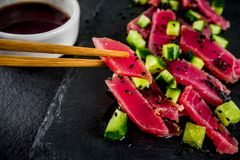 Tuna sashimi poke. With raw fresh fish, cucumber, black sesame seeds and soy sauce, black stone background copy space stock images