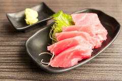 Tuna Sashimi. And wasabi in brown ceramic plate on wood table royalty free stock photos