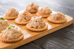 Tuna spread with cracker. On wood board stock photos