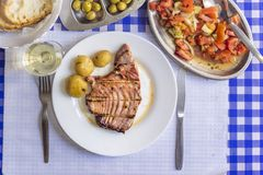 Tuna steak accompanied with potatoes, olives, tomato salad, brea. D and wine on white plate Royalty Free Stock Images