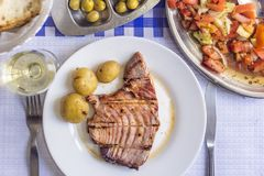 Tuna steak accompanied with potatoes, olives, tomato salad, brea. D and wine on white plate Royalty Free Stock Photos