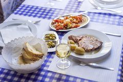 Tuna steak accompanied with potatoes, olives, tomato salad, brea. D and wine on white plate Stock Image