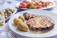 Tuna steak accompanied with potatoes, olives, tomato salad and w. Ine on white plate Royalty Free Stock Photos