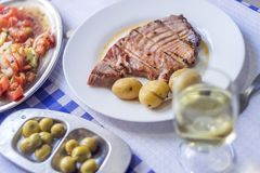 Tuna steak accompanied with potatoes, olives, tomato salad and w. Ine on white plate Royalty Free Stock Images