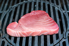 Tuna steak being grilled on the bbq. A large and still raw fresh tuna steak is being grilled on the bbq royalty free stock photos
