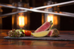 Tuna steak. Garnished with vegetables on stone plate Stock Photos