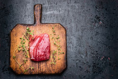 Tuna steak for grill or frying on wooden cutting board and dark rustic background with fresh herbst, top view,. Tuna steak for grill or frying on wooden cutting stock photo