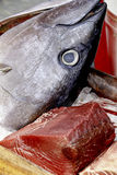 Tuna steak on a marketplace. A head and a piece of tuna in a marketplace Royalty Free Stock Photo
