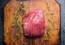 Tuna steak on rustic wooden background with fresh herbs, top view, close up. Royalty Free Stock Photos