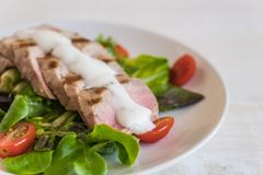 Tuna steak with salad. On wood table Royalty Free Stock Photography