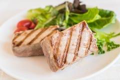 Tuna steak with salad. On wood table Stock Photos