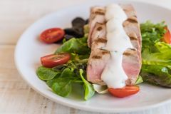 Tuna steak with salad. On wood table Stock Photo