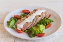 Tuna steak with salad. On wood table Royalty Free Stock Photo