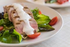 Tuna steak with salad. On wood table Royalty Free Stock Image