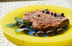 Tuna steak served with olives, basil and capper in yellow plate in blurry background Stock Photos