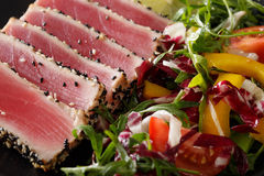 Tuna steak in sesame seeds with fresh vegetable salad close-up. Stock Photo