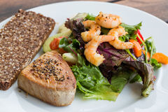 Tuna Steak and vegetable salad v2. Tuna Steak and vegetable salad with shrimps and bread Royalty Free Stock Image
