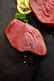 Tuna Steaks Seasoned cruda con le erbe ed il limone fotografia stock
