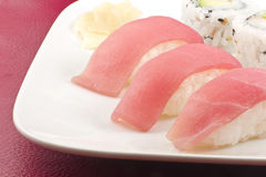 Tuna Sushi California Roll. Authentic Japanese cuisine tuna sushi with california roll, wasabi, and ginger Royalty Free Stock Photo