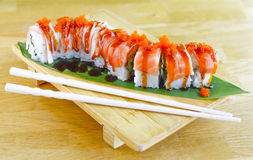 Tuna Sushi Roll. Image of a tuna sushi roll on a wodden platter with chopsticks Stock Images