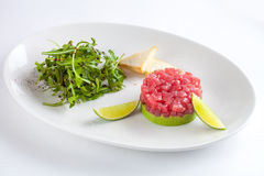 Tuna tartar garnished with lime and arugula. On white background Stock Image