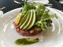 Tuna Tartar and Avocado Slices. Tuna tartare recipe is a dish made from raw tuna that has been cut into small pieces before serving. It can be chopped, cut into Stock Image