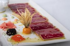 Tuna tataki on olive oil background accompanied by caviar. The tuna tataki on olive oil background accompanied by caviar stock photo