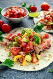 Tuna Tortilla with avocado, fresh salsa, limes, greens, parsley, tomatoes, red yellow pepper. colorful vegetable Stock Photography