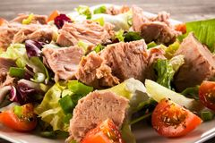 Tuna and vegetable salad. On wooden background Royalty Free Stock Photos