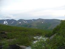 Tundra, montañas, río y nubes imagen de archivo