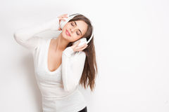 Tune in. Gorgeous young brunette enjoying music in white headphones royalty free stock photography