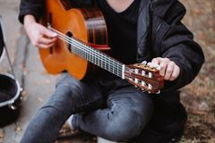 Tune and play. Tuning acoustic guitar and play musik in park royalty free stock photography