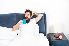 Tune in to new day. Humanity runs on coffee. Morning awakening better with cup coffee. Relax and rest. Man brutal. Handsome hipster relaxing bedroom drink royalty free stock photo