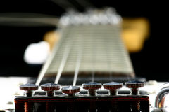 Tune it up. Close up at fine tuners of electric guitar with fretboard in the background Royalty Free Stock Image