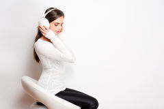 Tuned in. Portrait of a beautiful young brunette woman listening to music in headphones royalty free stock image