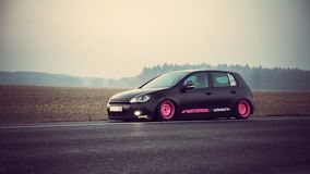 Tuned volkswagen golf 6 on a background of a field and sunset on the road stock photo