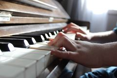 Tunes. Child's hands playing a piano Royalty Free Stock Photography