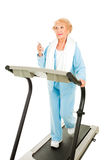 Tunes on the Treadmill. Senior woman listens to her mp3 player while exercising on the treadmill.  Isolated on white Stock Photo