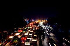 Tung biltrafik i centret av Delhi, Indien på natten Royaltyfri Fotografi