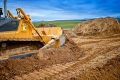 Tung bulldozer och röd sand för för grävskopapäfyllning och flyttning Arkivbild