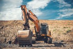 Tung grävskopa på huvudvägkonstruktionsplats, hinkdetaljer, smuts och grus lite varstans Royaltyfria Bilder