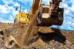 Tung jord för konstruktionsgrävskopaflyttning arkivfoto