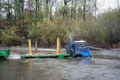 Tung lastbil som vadar över floden på högt vatten, Ryssland Arkivbild