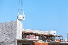 Tung påfyllning som hänger på konstruktionsplats av tegelstenbyggnad Fotografering för Bildbyråer