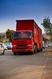 Tung röd lastbil för gods på genomresa - Royaltyfri Foto